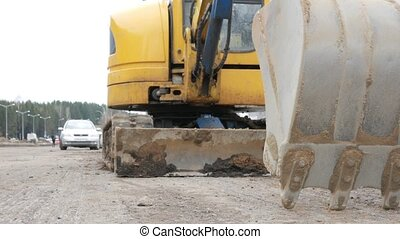 The excavator stands on the road with the bucket lowered. Road works are carried out in the city