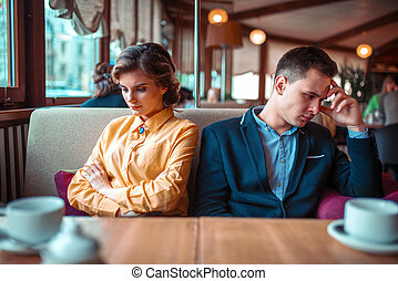 Couple in a bad mood sitting in restaurant. Man and woman...