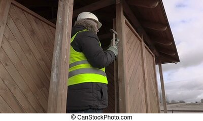 Worker hammering  nail in wooden board