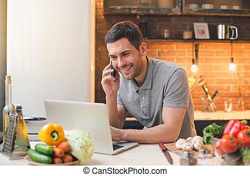 Young Man Vegan Meal Preparation Using Laptop