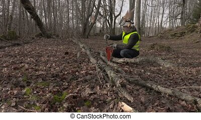 Worker checking chainsaw near fallen tree in park