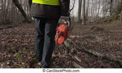 Worker with chainsaw start walking near fallen tree in park