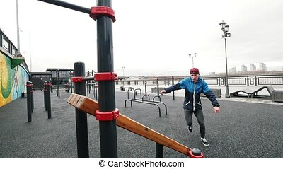 Acrobatic teenager jumping in sports grounds - performing a...