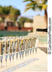 Many glasses of champagne or prosecco near resort pool in a...
