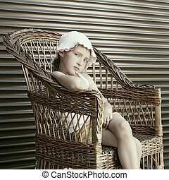 Beautiful small girl seating in wicker chair