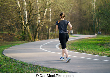 Running woman in park in spring training, girl in sporty running clothes.