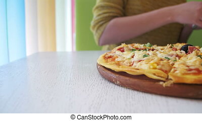 Women's Hands Cut a Slice of Pizza in Cafe. Dolly shot -...