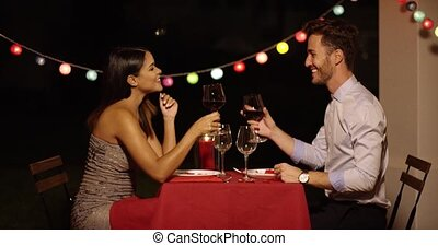 Good looking couple toasts with glasses of wine across red...