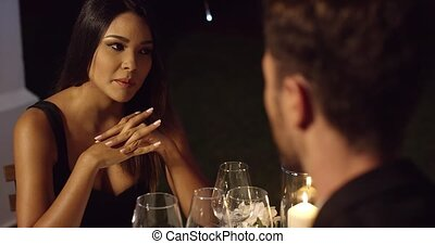 Elegant young woman enjoying a dinner date talking to a...