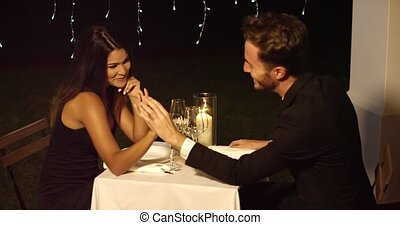 Handsome couple holds hands across dinner table in fancy...