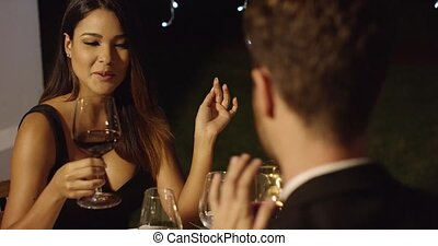 Elegant young woman chatting with her date during a romantic...