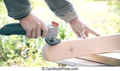 Grinding a wooden plank with an orbital detail sander -...