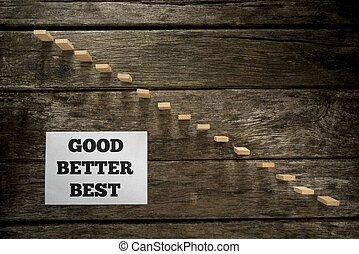 Top view of Good Better Best message written on white paper card