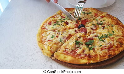 Women's Hands Cut a Slice of Pizza and Put it on a Plate in...