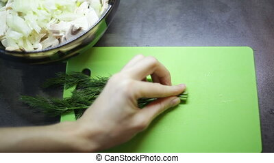 Woman slicing greens on a cutting board.