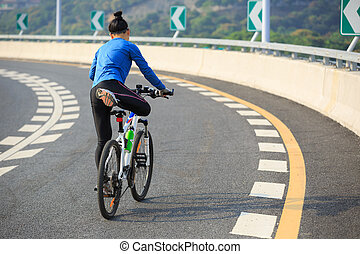 one woman cycling mountain bike on road