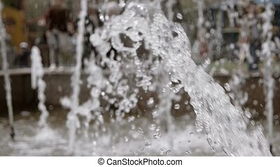 Water drops and splashes fly in an air. City park fountain...