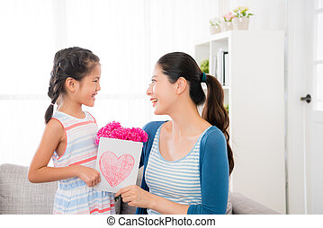 chinese mother and daughter look at each other - asian...