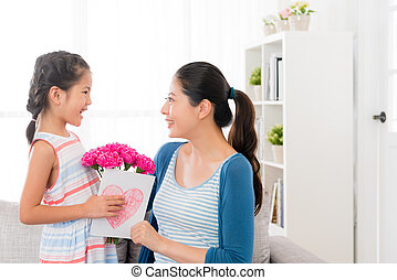 little girl prepare a pink carnation bouquet - smiling asian...