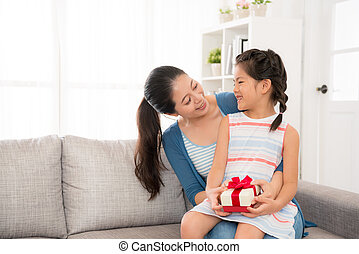 mother sitting on the couch holding daughter