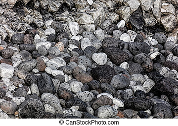 Rounded volcanic black stones on the beach of the...