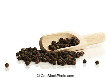 black peppercorns with a small wooden shovel from side on...