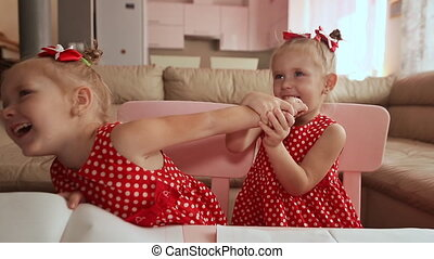 Two charming twin sisters pamper each other, playing with their hands together.