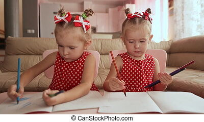 Two smiling little sisters twins draw at the table with colored pencils.