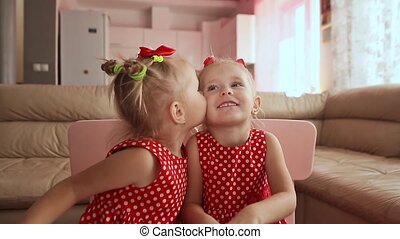 Two cute twin sisters are dressed in red polka-dot dresses. Playing together kiss each other smiling.
