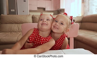 Two cute twin sisters are dressed in red polka-dot dresses....