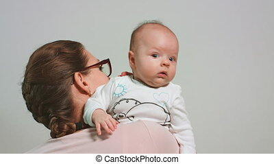 Mother Holds the Baby on Her Shoulder
