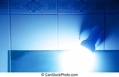 detail of bathroom lamp and light reflection in blue tones.