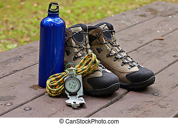 Climbing gear - Hiking boots, canteen and compass in the...