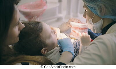 Young mother with cute boy sitting in dentist chair. Woman...