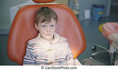 Cute little boy at doctor s office and waiting. Male looking around sitting in dentist chair before dental check-up.