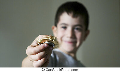 Boy holding fidget spinner golden toy - Young boy play with...