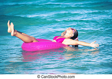 Fun with tube - Funny woman relaxing on pink inner tube