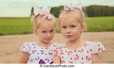 Little sisters twins chew bread near the road near the field. Far Forest.