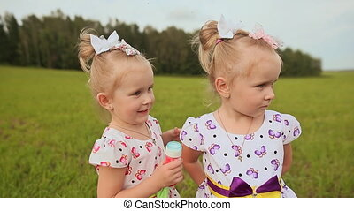 Cute happy little sister twins embrace fun outdoors in the summer.