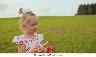 Charming little girl in a white dress blowing soap bubbles in summer on a meadow.