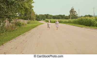 Two little twins sisters to run one after the other on the...