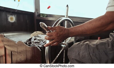 Hands of the yacht driver turn the steering wheel. Close-up