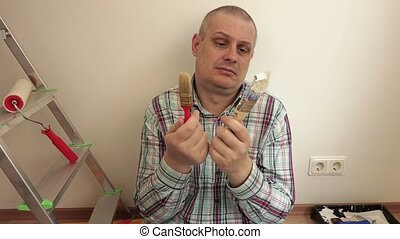 Man with the painting brushes in the hands of