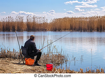A fisherman with a fishing rod sitting on a chair on the...