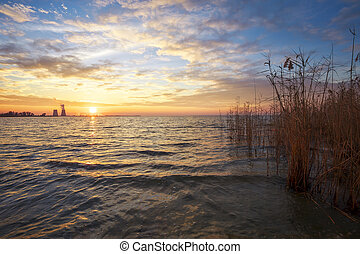 Beautiful landscape with sunset sky, reservoir, reeds and power plant.