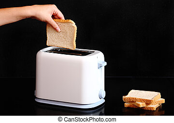 Hand putting bread to toaster