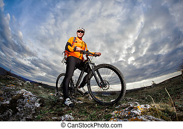 Portrait of the young cyclist standing with bike on the rocks against dramatic sky with clouds.