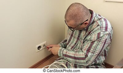 Man with screwdriver near electrical sockets