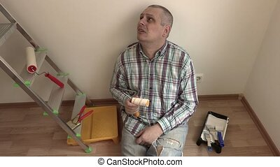 Man with paint roller sitting and thinking