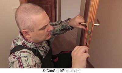 Worker with screwdriver near door lock